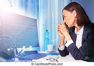 Woman looking at screen of computer in the office