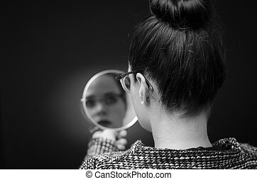woman looking at self reflection in mirror Stockfoto: