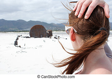 Woman looking at Shipwreck Kakapo at the beach of kommetjie