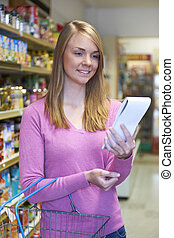 Woman Looking At Shopping List In Supermarket
