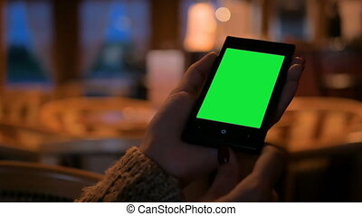 Woman looking at smart phone phone with green screen in cafe
