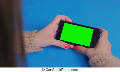 Woman looking at smartphone with green screen