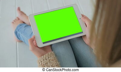 Woman looking at tablet computer with green screen