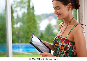 Woman looking at tablet pc - Pretty young smiling woman...