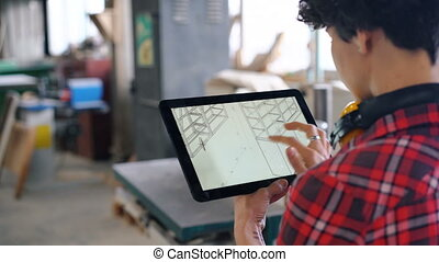 Woman looking at tablet screen checking furniture design in wood workshop