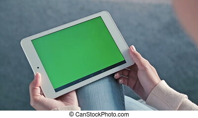 Woman looking at tablet with green screen
