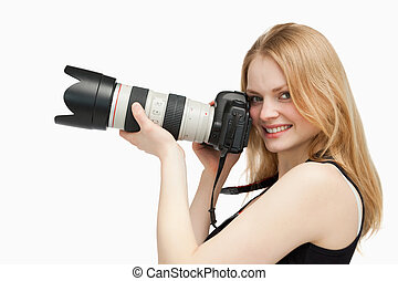 Woman looking at the camera while holding a camera