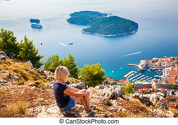 woman looking at the Dubrovnik and island Lokrum