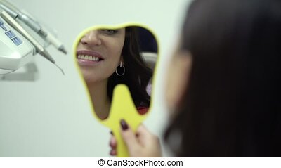 Woman looking at the mirror in dental clinic