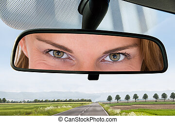 Woman Looking At The Mirror Of A Car