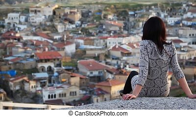Woman looking at the panorama - A woman sitting and looking...