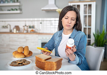 Woman looking at the pills while sitting in the kitchen