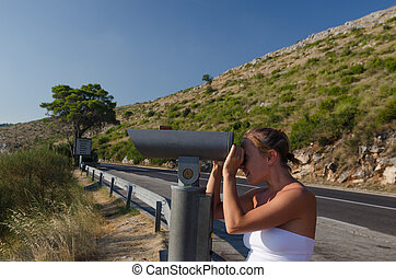 Woman looking at the scenic lookout binoculars