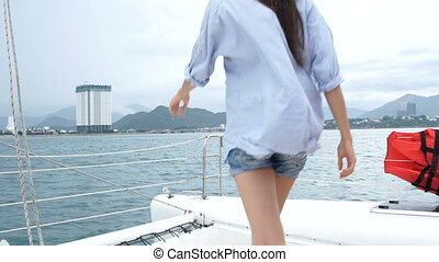 Woman looking at the sea,rise hands and dancing while enjoying a cruise on yacht