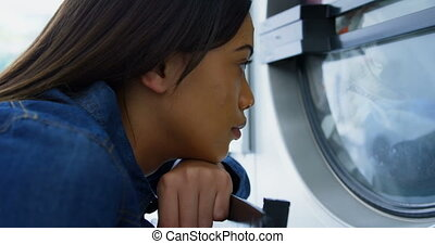 Woman looking at washing machine at laundromat 4k -...
