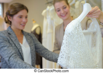 Woman looking at wedding dress in a store