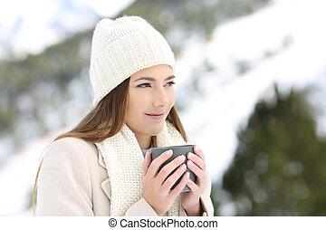 Woman looking away holding a coffee mug in winter