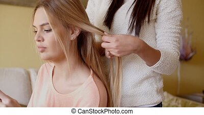 Woman Looking Away While Friend is Fixing her Hair