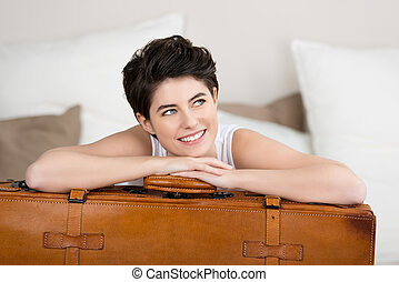 Woman Looking Away While Leaning On Suitcase