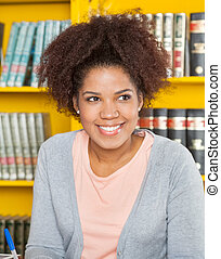 Woman Looking Away While Smiling In University Library