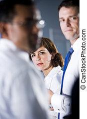 Woman looking between two businessmen