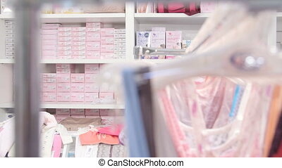 Woman looking for clothes in baby and maternity shop