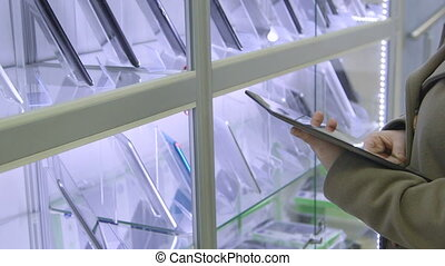 Woman looking for digital tablet computer in electronics store