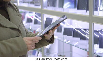 Woman looking for digital tablet in computer store