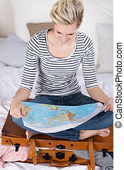 Woman looking for exotic travel destinations sitting cross legged on her suitcase on her bed reading a world map