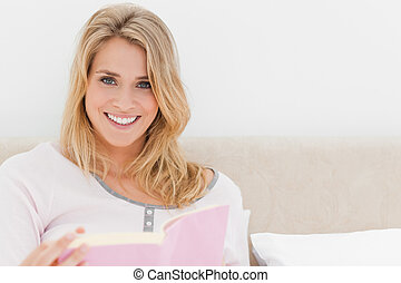 Woman looking forward with book in hand smiling