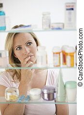 Woman Looking in Medicine Cabinet - A young woman is looking...
