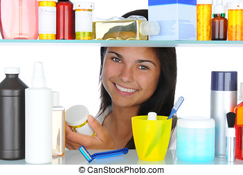 Woman Looking in Medicine Cabinet - Young woman looking in...