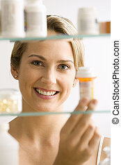 Woman Looking in Medicine Cabinet - A young woman looks...