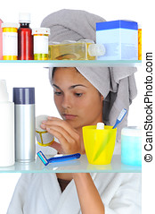 Woman Looking in Medicine Cabinet - Young woman looking at...