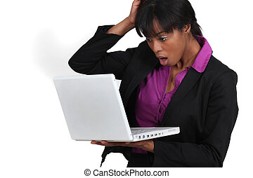 Woman looking in shock at her laptop