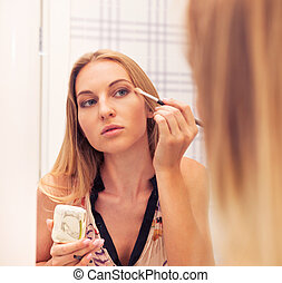 Woman looking in the mirror and putting make up on