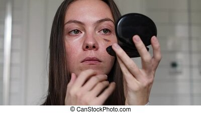 Woman looking in the mirror at bruise eye close-up portrait....