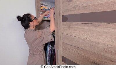 Woman looking in wardrobe and close door