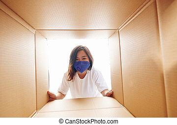 Woman looking inside of cardboard box