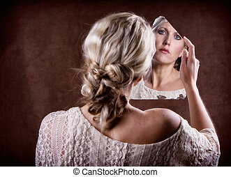 woman looking into a broken mirror