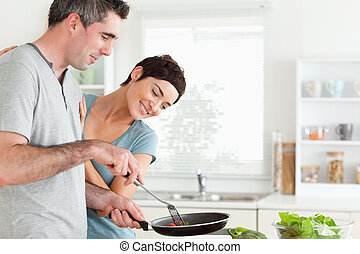 Woman looking into a pan her husband is holding