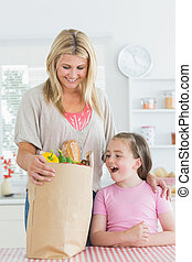 Woman looking into grocery bag beside smiling daughter