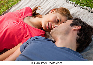 Woman looking into her friends eyes while lying on a quilt