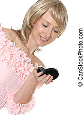 Woman looking into mirror - An adult woman checks her makeup...
