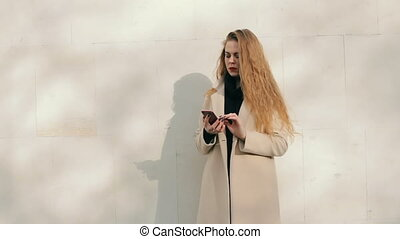 Woman looking like Nicole Kidman with phone buying online outdoors