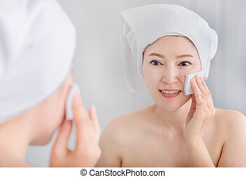 woman looking mirror and cleaning her face with cotton -...