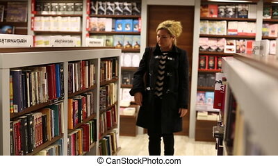 bookstore - woman looking new book at bookstore, Steadicam...