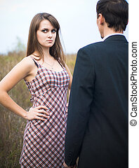 Woman looking offended over man shoulder