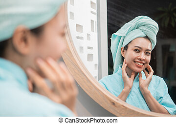 Woman looking on reflection in the mirror with a clean fresh skin touches