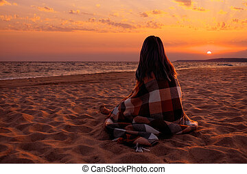 Woman looking on sunset over the sea.